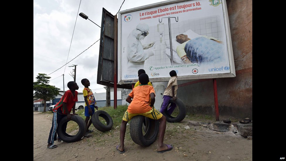 "Children with tyres look at an Ebola poster reading: ""Let's apply the protective measures together"" - Abidjan, Ivory Coast, Sunday 24 August 2014"
