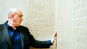 Man touching a war memorial with his hand