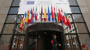 A woman passes the entrance of the European Council headquarters in Brussels, 29 August