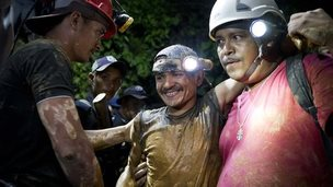 A rescued miner, center, is greeted by another miner while being helped by a rescue worker as he leaves the El Comal gold and silver mine in Bonanza, Nicaragua, Friday, Aug. 29