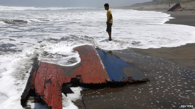 "A youth stands near a piece of wreckage of a boat which Indonesian police said was carrying migrants to Australia and sank off the Indonesian coast, at Agrabinta beach on the outskirts of Sukabumi, Indonesia""s West Java province in this September 28, 2013"