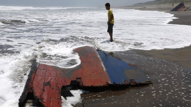 """A youth stands near a piece of wreckage of a boat which Indonesian police said was carrying migrants to Australia and sank off the Indonesian coast, at Agrabinta beach on the outskirts of Sukabumi, Indonesia""""s West Java province in this September 28, 2013"""