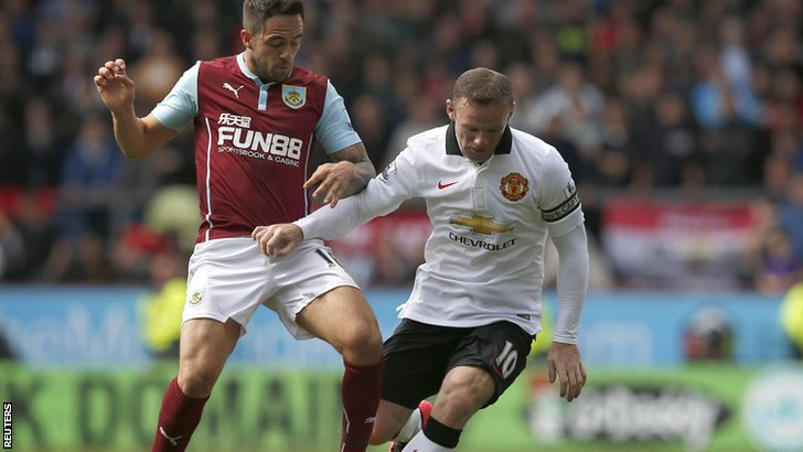 Danny Ings challenges Wayne Rooney for the ball