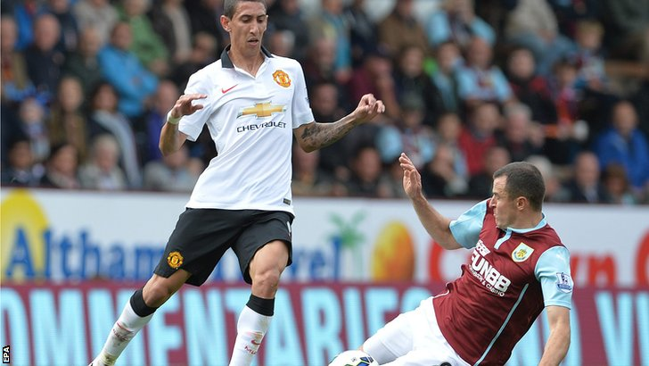 Angel Di Maria is challenged for the ball by Dean Marney