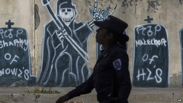 A police officer walks by gang graffiti depicting gang member deaths.  April 14 2014