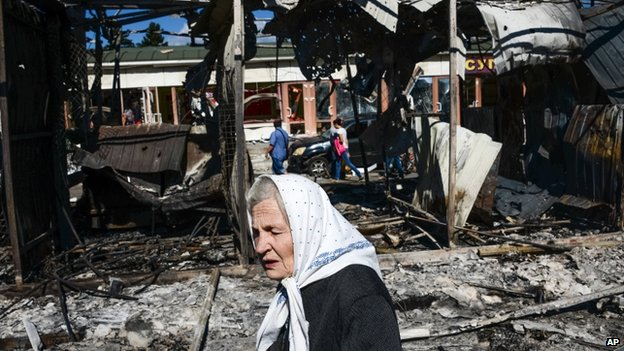 A woman passes by shops destroyed by shelling in Donetsk, eastern Ukraine. Photo: 30 August 2014
