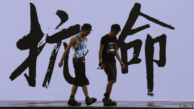 "Pro-democracy activists walk past a backdrop with Chinese characters that read ""disobedience"""