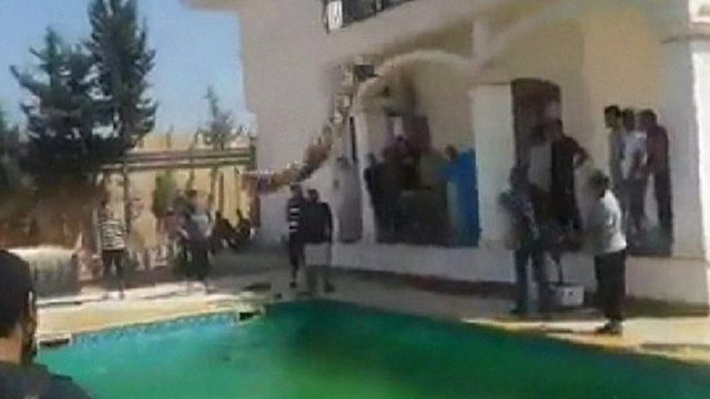 Men jump into a swimming pool at the US embassy in Libya