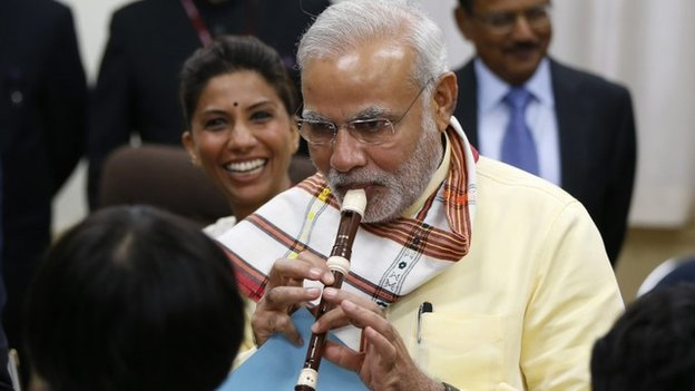 India's Prime Minister Narendra Modi (C) tries to play a soprano recorder before school children at a music class during a visit at Taimei Elementary School in Tokyo, September 1, 2014.
