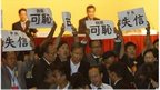 Pro-democracy lawmakers display placards against Li Fei, deputy secretary general of the National People's Congress' Standing Committee, during a briefing session in Hong Kong Monday, 1 Sept 2014