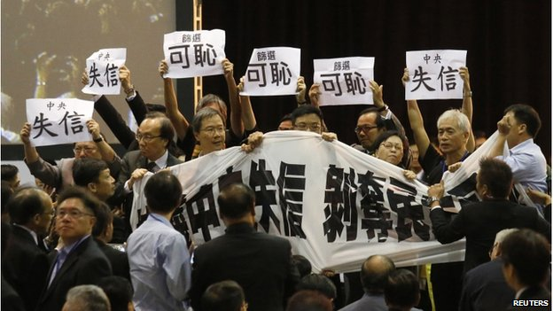 Pro-democracy lawmakers hold up a banner and placards to protest as Li Fei (not pictured), deputy general secretary of the National People's Congress (NPC) standing committee, speaks during a briefing session in Hong Kong 1 September 2014.