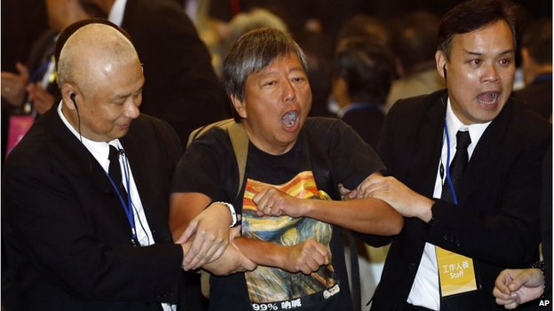 "Pro-democracy lawmaker Lee Cheuk Yan (centre) is taken away by security guards after a protest against Li Fei, deputy secretary general of the National People's Congress"" Standing Committee, in Hong Kong Monday, 1 Sept 2014."