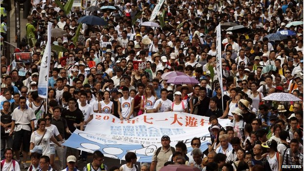 """Protesters hold a banner which reads """"2014 July 1 mass march"""" to demand universal suffrage in Hong Kong on 1 July 2014, the day marking the 17th anniversary of the territory's handover to China."""