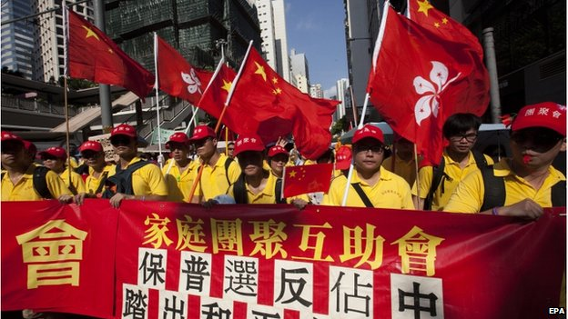 """Pro-China protestors, opponents of the pro-democracy """"Occupy Central"""" movement, march behind a banner reading """"Reunited Families Support Group, Pro-Universal Suffrage, Make a First Step for Peaceful Universal Suffrage"""", in Central District, Hong Kong, China, 17 August 2014"""