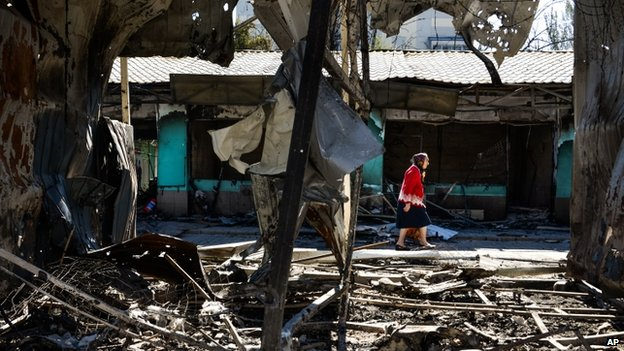 Woman walks past damaged buildings in Donetsk (30 August 2014)