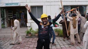 Pakistani protesters hold sticks and chant slogans after intruding into the state television building in Islamabad, Pakistan, Monday, Sept. 1, 2014.