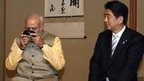 India's Prime Minister Narendra Modi enjoys a cup of green tea next to Japan's Prime Minister Shinzo Abe  during a tea ceremony at the Omotesenke, one of the main schools of Japanese tea ceremony, in Tokyo