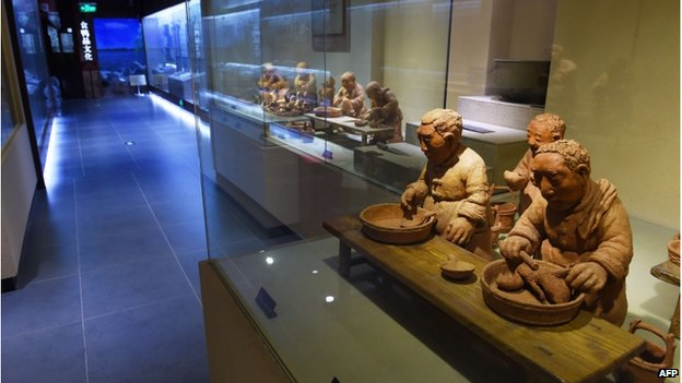 This photo taken on 24 July 2014 shows clay figures portraying the production of Peking Duck, in the museum at the Quanjude restaurant in Beijing.
