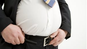 Obese man struggling with belt