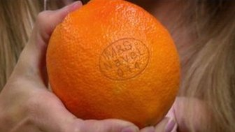 An orange labelled using a laser machine
