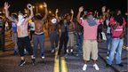 Demonstrators gesture with their hands up after protests in reaction to the shooting of Michael Brown turned violent near Ferguson, Missouri, 17 August 2014