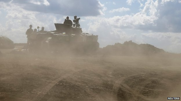 Ukrainian army servicemen around an armoured vehicle are seen through dust raised by passing vehicles near Debaltseve, Donetsk region, on 29 August 2014.