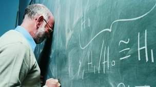Teacher leans head on board