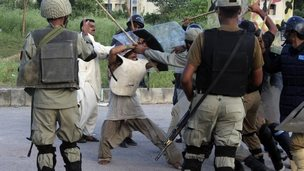 Police beat a protester during clashes in Islamabad