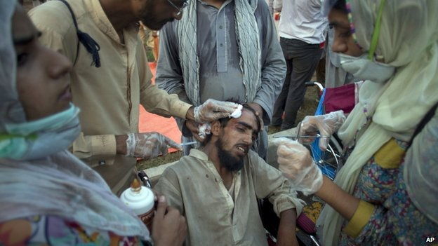 Pakistani volunteers treat an injured protester beaten by police during a clash in Islamabad (1 September 2014)
