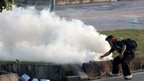 A protester picks up a tear gas canister to throw back towards police during a clash in Islamabad (1 September 2014)