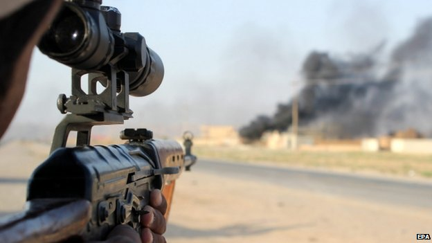 A member of the Iraqi Shiite militia, Kataib Hezbollah (Hezbollah Brigades), aims his rifle during fighting against Islamic State (IS) fighters, in Amerli town (1 September 2014)