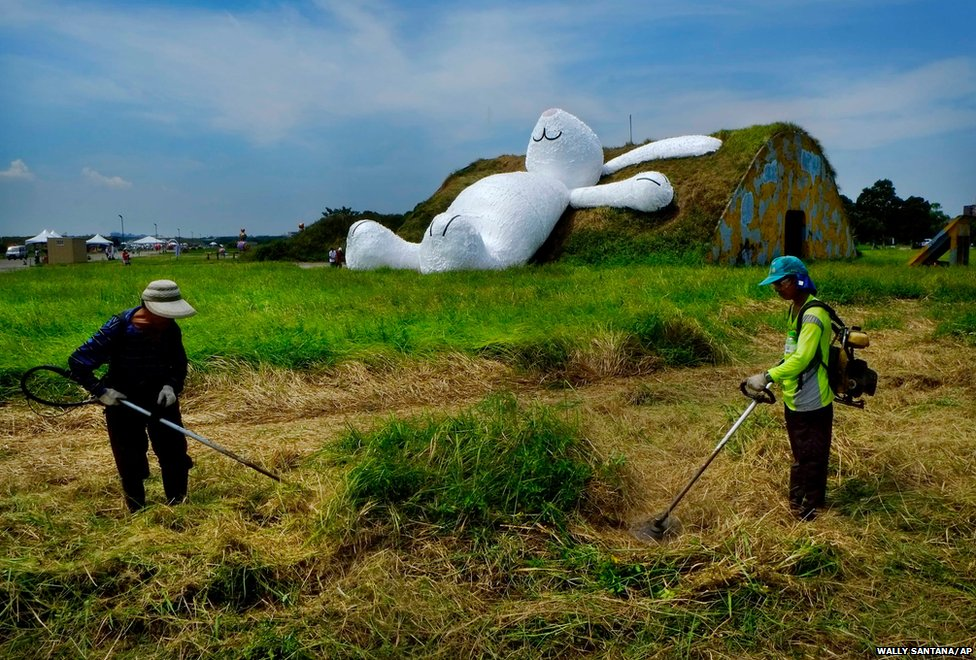 Landscapers trim grass in front of Dutch artist Florentijn Hofman's white rabbit sculpture