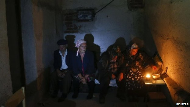 Local residents sit in a basement used as a shelter from artillery fire, in the village of Spartak, on the outskirts of Donetsk, Ukraine, 1 September 2014