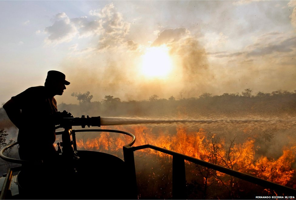 A soldier tries to extinguish a fire at the park Floresta Nacional in Brasilia, Brazil