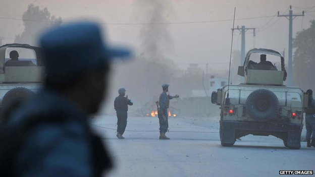 Afghan policemen keep watch as smoke billow in the background after an attack by Taliban militants on the Afghan intelligence service office in Jalalabad on 30 August 2014.