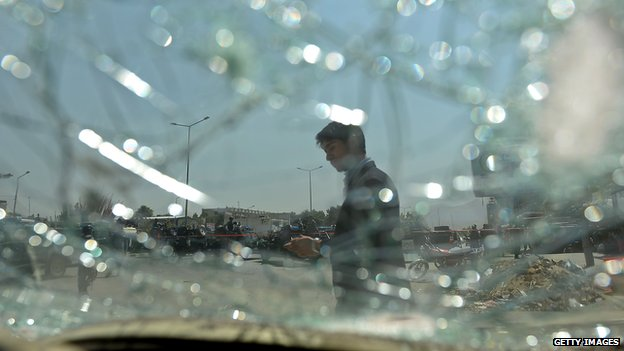 An Afghan bystander is seen through broken glass of car at the site of a suicide attack in Kabul on 10 August 2014.