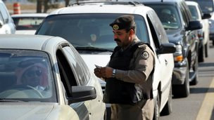 A Saudi policeman checks the ID card of a driver at a checkpoint in the east of the country - 25 November 2011