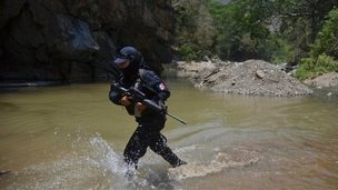A federal police officer crosses a river on the outskirts of Arteaga during a search for Knights Templar leader Servando Gomez (26 April 2014)