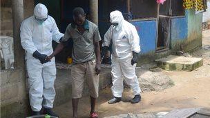 Nurses helping man with Ebola