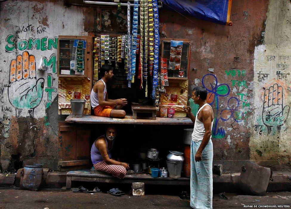 A man drinks tea while standing next to a roadside tea shop in Calcutta, India