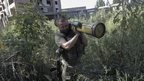 A Ukrainian policeman removes a weapon found in Sloviansk, Donetsk region, 2 September