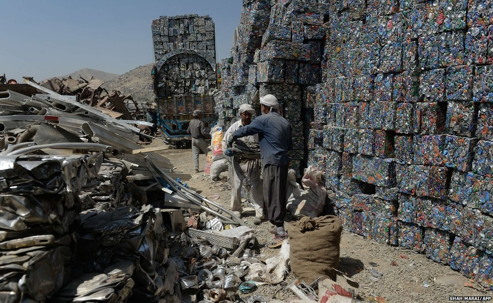 Afghan day-labourers load recyclable cans onto a truck at a scrap yard on the outskirts of Kabul
