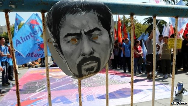 A mask depicting the face of Ethem Sarisuluk hangs on a police barrier outside the courthouse in Ankara on 3 September 2014