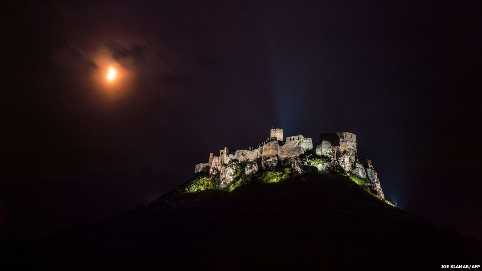 Moon glows through the clouds over the ruins of Spis Castle in the Eastern Slovakia's village of Zehra