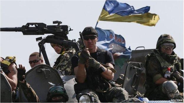 Ukrainian servicemen ride on armoured vehicles near Slaviansk