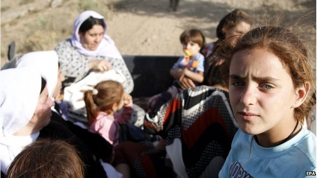 Yazidi refugees sit in a truck awaiting transfer as they flee from Iraq