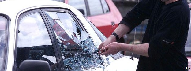 A car window being smashed by a police officer during a car crime demonstration