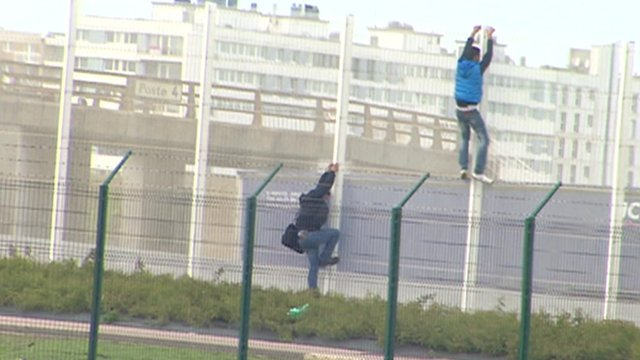 People scale fence