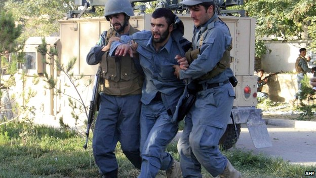 Afghan policemen help an injured comrade at the site of a suicide bomb attack in Ghazni Province 4 September 2014.
