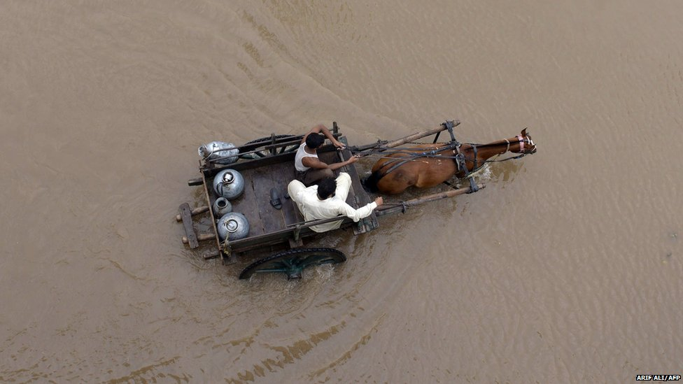 Pakistani milkmen ride on a horse-cart through floodwaters following heavy rain in Lahor